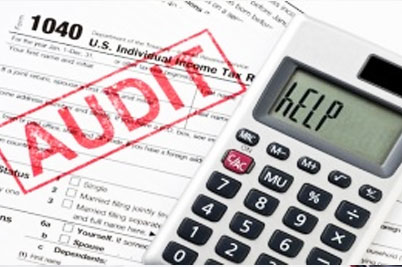 audit stamped paperwork with calculator