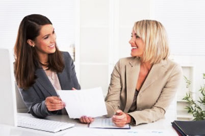 Women discussing bookkeeping while smiling
