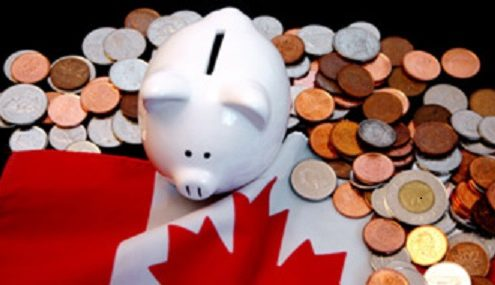 White piggybank on Canadian flag with coins around it