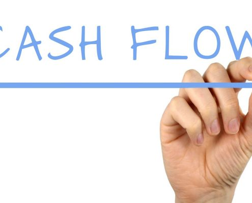 Hand writing CASH FLOW with blue marker