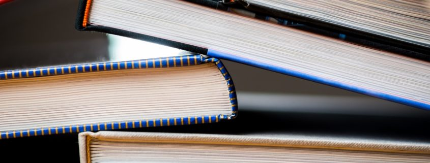 Books stacked messily, minute books graphic