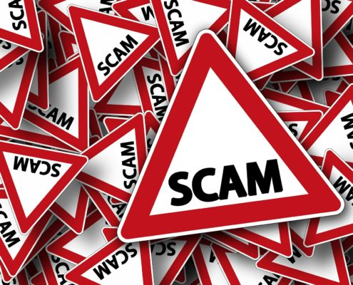 red and white warning signs with the word Scam