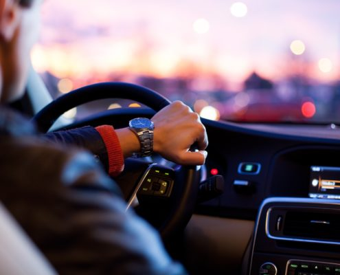 man driving car with one hand at sunset