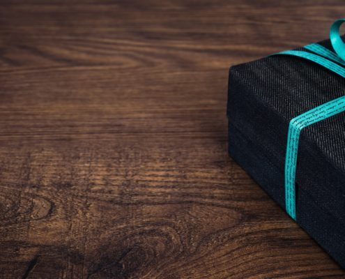 black gift with blue ribbon on wooden surface
