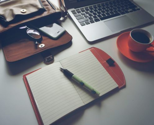 office desktop with laptop notebook coffee and bag