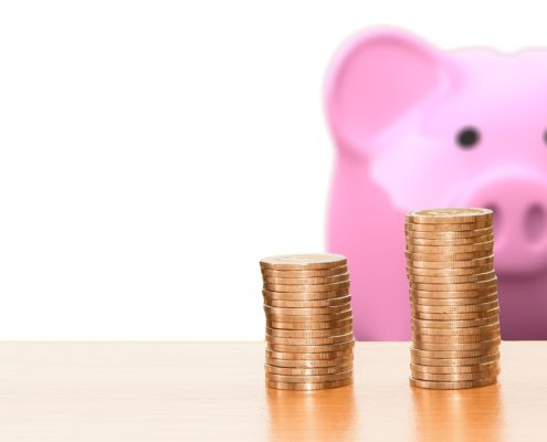 stack of coins in front of pink piggy bank